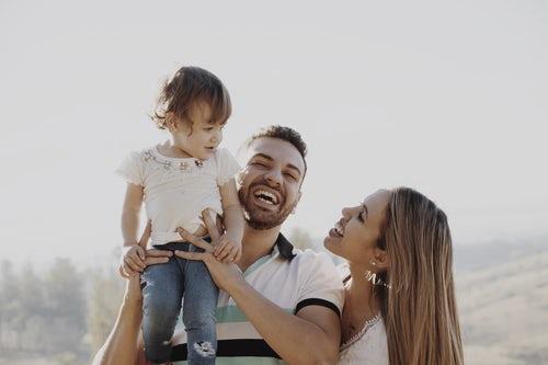 男性が子供を抱っこして、女性が子供を笑顔で見ている