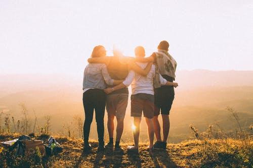 夕陽を見て肩を組む四人組