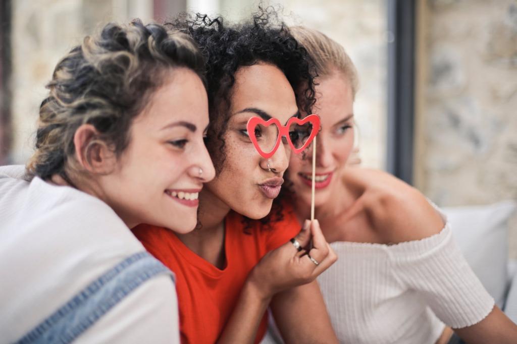 ハートの眼鏡をかけて写真を撮る女性たち