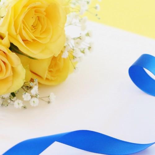青色のリボンと黄色の花が置かれている様子