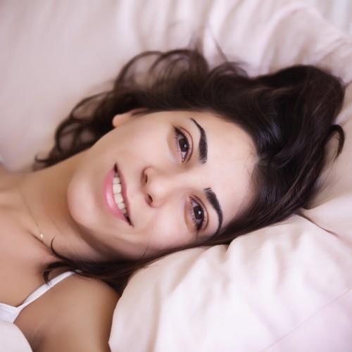 ベッドに横たわっている笑顔の女性