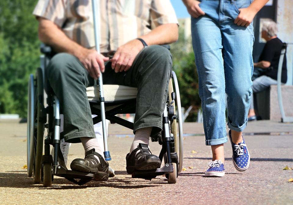 車椅子に乗った人とウォーキングしている人
