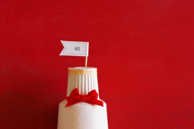 還暦祝いのケーキと赤い背景