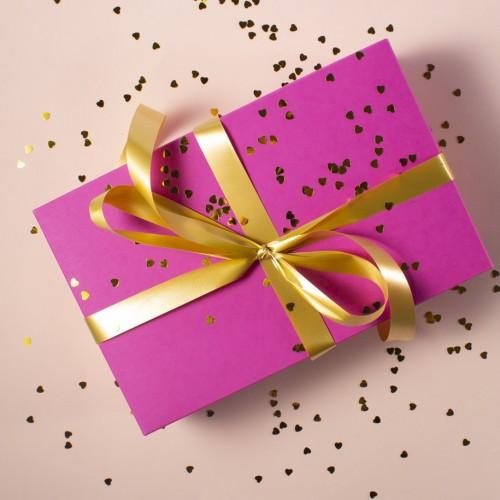ピンクの箱にゴールドの紐でラッピングされたプレゼント