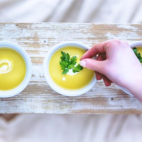 スープに彩りを加えようとする女性の手