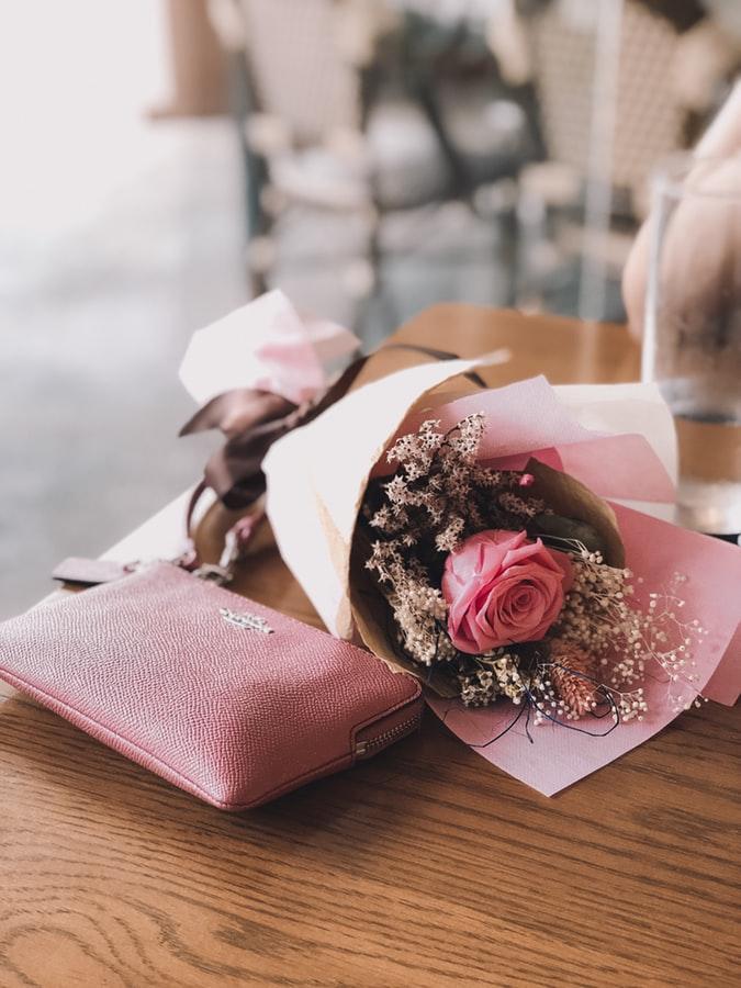 テーブルの上に置かれた花束とピンクの財布