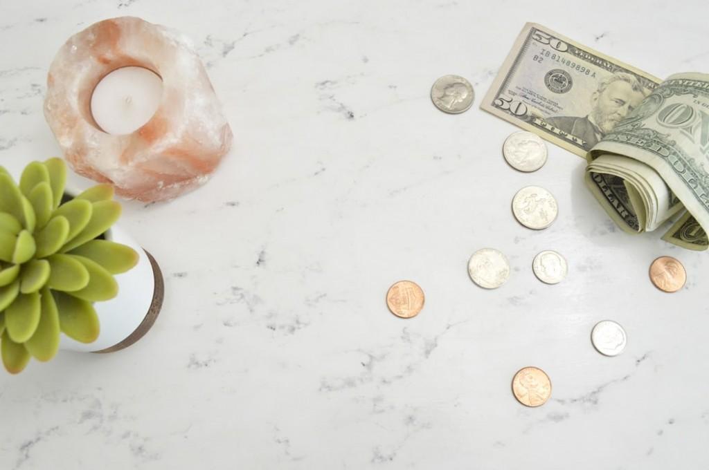 散らばったアメリカのお札と小銭、観葉植物とキャンドル