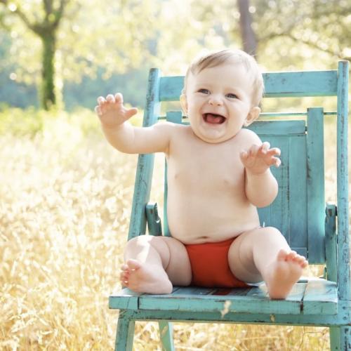 外でグリーンの椅子に座った赤ちゃん