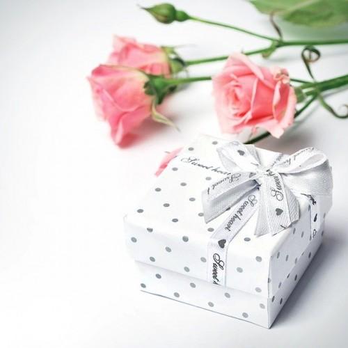 ピンクのバラと白いリボンで結ばれたドット柄のギフトボックス